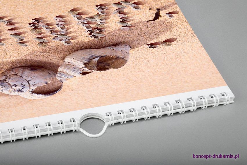 Ścienny kalendarz z zawieszką połączony białą estetyczną spiralą.