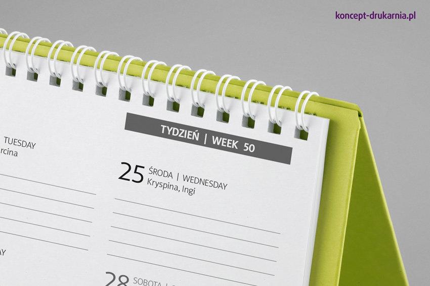 Karty kalendarza połączone są ze stojakiem za pomocą białej metalowej spirali.