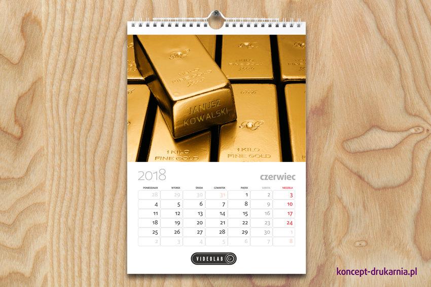 Powieszony na ścianie personalizowany kalendarz spiralowany z zawieszką.