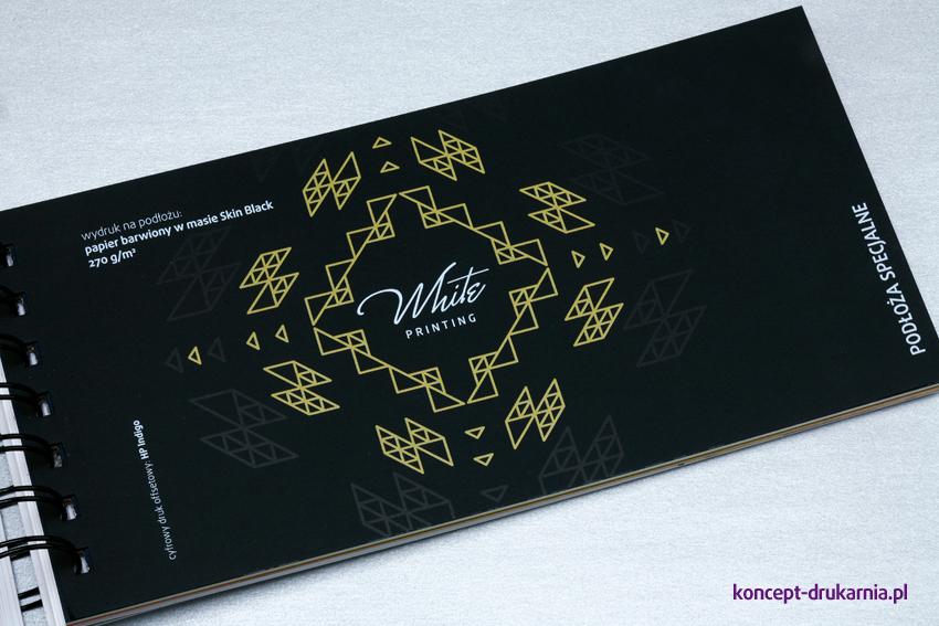 Przykład zadruku CMYK i kolorem białym na czarnym papierze barwionym w masie Skin Black 270 g/m2.